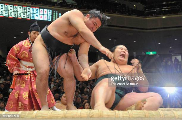 Satoyama throws Kagamio on day four of the Grand Sumo New Year Tournamnet at Ryogoku Kokugikan on January 15 2014 in Tokyo Japan