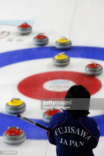 Satsuki Fujisawa of Japan inspects the stones and the play area rings in the match between Japan and Latvia during Day 2 of the Titlis Glacier...
