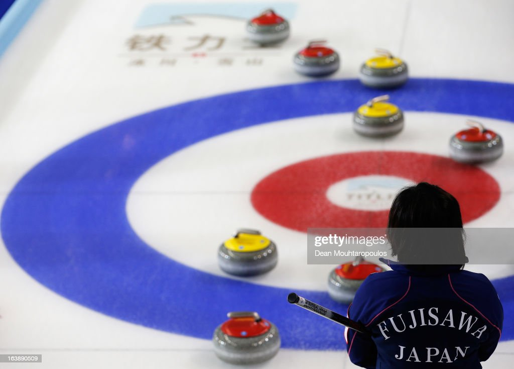 Satsuki Fujisawa of Japan inspects the stones and the play area rings in the match between Japan and Latvia during Day 2 of the Titlis Glacier Mountain World Women's Curling Championship at the Volvo Sports Centre on March 17, 2013 in Riga, Latvia.