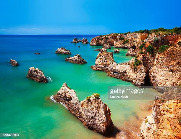saturated image of a colorful algarve beach in portugal - algarve stock photos and pictures