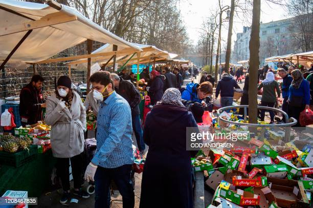 Saturday shoppers crowd the Yorck Strasse market in Berlin on March 28, 2020 amid the novel coronavirus pandemic. - Police patrolled parks and public...