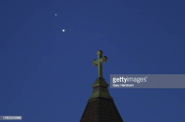 Saturn and Jupiter set behind a church ahead of their conjunction that is being called The Christmas Star next week on December 18, 2020 in Jersey...