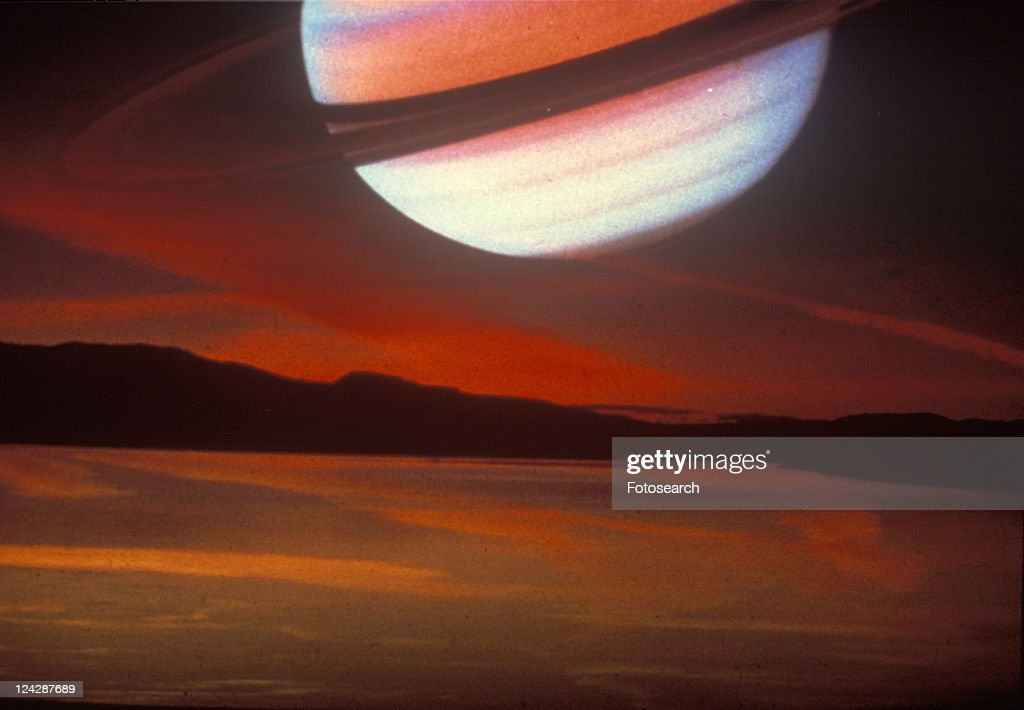 Saturn superimposed on a cloudy sunset sky : Stock Photo