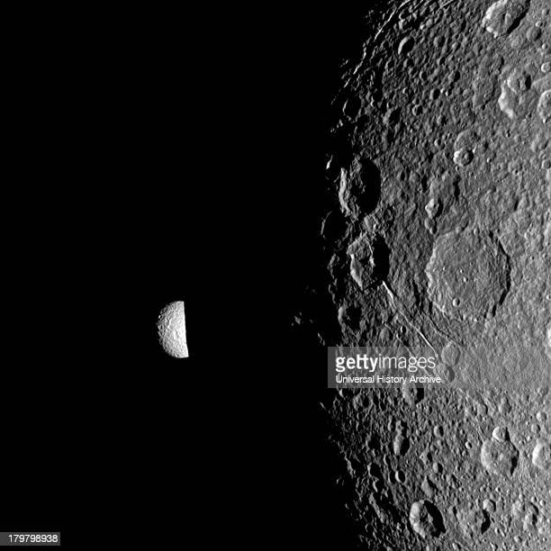 Saturn's moon Mimas peeks out from behind the night side of the larger moon Dione in this Cassini image