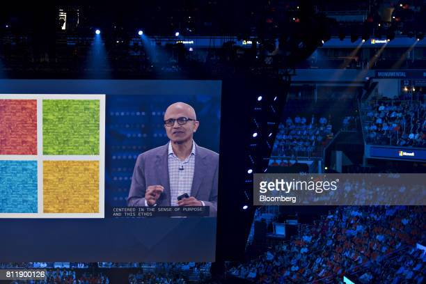 Satya Nadella chief executive officer of Microsoft Corp is seen speaking on a large screen as attendees listen during the Microsoft Inspire partner...