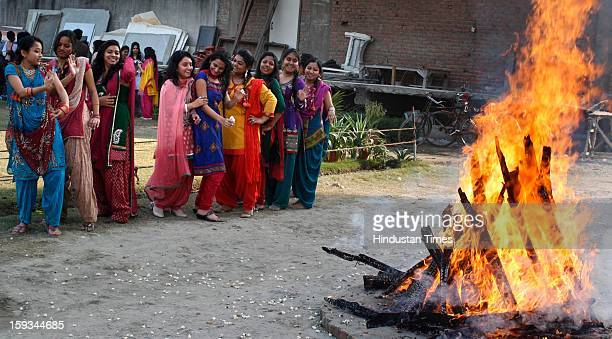 Satyam Fashion Institute students dance around a fire to celebrate the Lohri festival at Sector 62 on January 12 2013 in Noida India Lohri marks the...