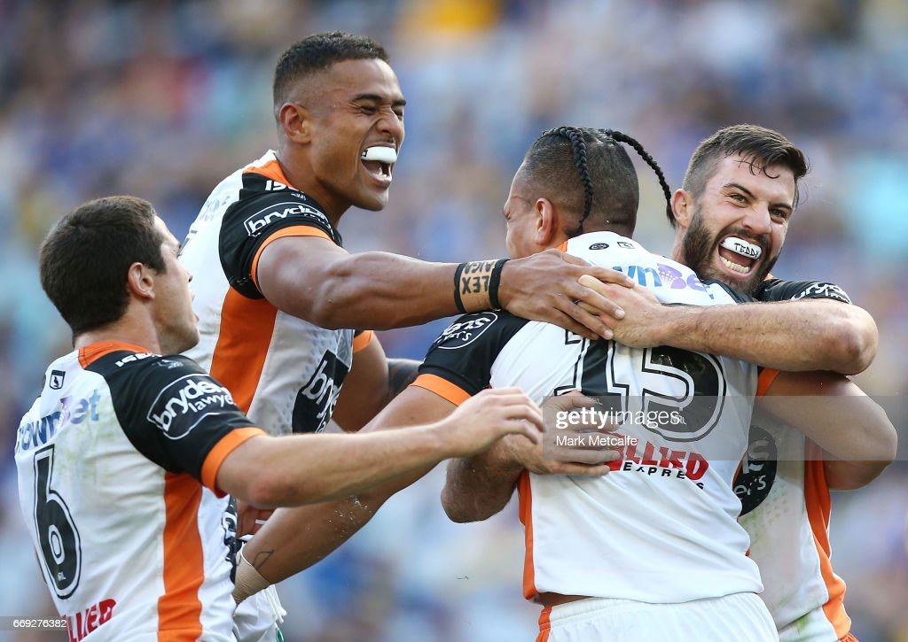 Sauaso Sue of the Tigers celebrates scoring a try with team mates during the round seven NRL match between the Parramatta Eels and the Wests Tigers at ANZ Stadium on April 17, 2017 in Sydney, Australia.