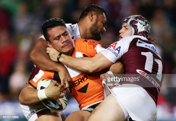 Sauaso Sue of the Tigers is tackled during the round 18 NRL match between the Manly Warringah Sea Eagles and the Wests Tigers at Brookvale Oval on...