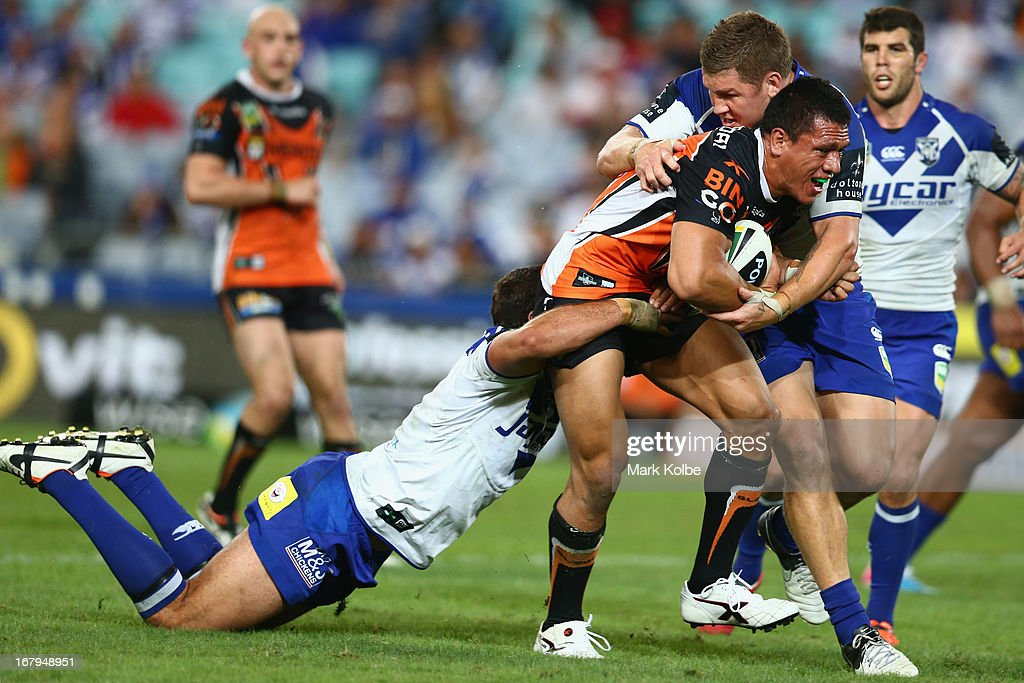 Sauaso Sue of the Tigers is tackled during the round eight NRL match between the Bulldogs and the Wests Tigers at ANZ Stadium on May 3, 2013 in Sydney, Australia.