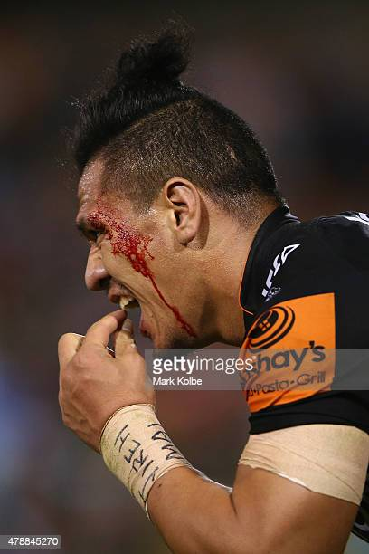 Sauaso Sue of the Wests Tigers grimaces as he feels his teeth during the round 16 NRL match between the Wests Tigers and the Penrith Panthers at...