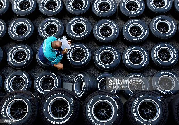 A Sauber crew member works on Bridgestone tires behind the pits at Indianapolis Motor Speedway 25 September during preparations for the Formula One...