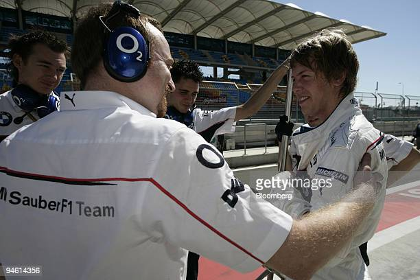 Sauber mechanics congratulate Sebastian Vettel who was fastest at the second practice session on the first practice day for the Formula 1 GP in...