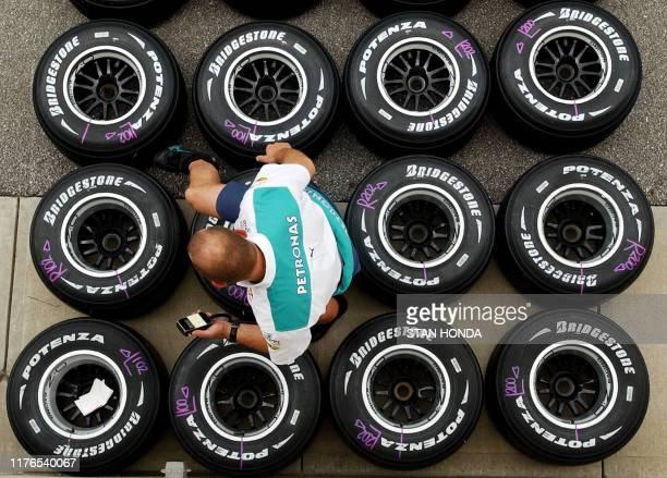 Sauber Petronas crew member checks the pressure on Bridgestone tires as he prepares for the 2004 United States Grand Prix, 17 June at Indianapolis...