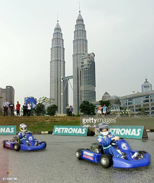 Sauber Petronas Formula One drivers Kimi Raikkonen and Nick Heidfeld race in gokarts with the Petronas Twin Towers in the background during a...