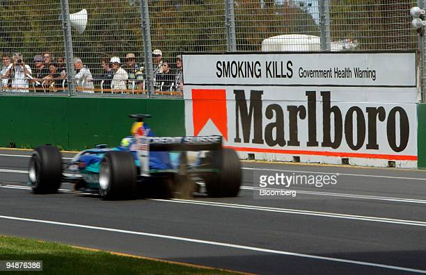 Sauber team Formula 1 car passes by an advertising billboard for Philip Morris Inc's Marlboro cigarettes during a practice round at the Australian...