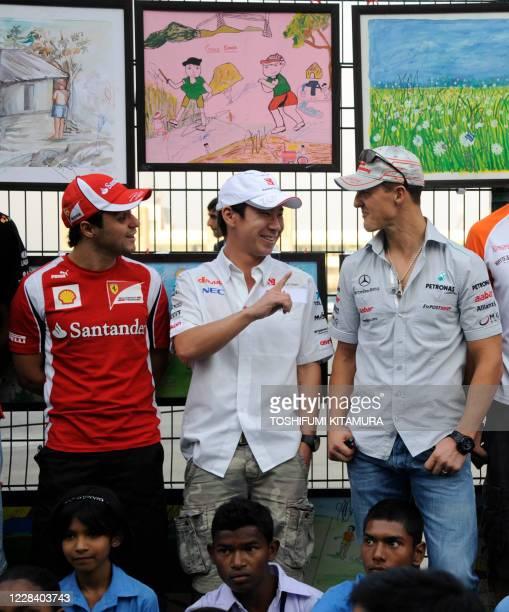 Sauber-Ferrari driver Kamui Kobayashi of Japan chats with Mercedes driver Michael Schumacher of Germany and Ferrari driver Felipe Massa of Brazil...
