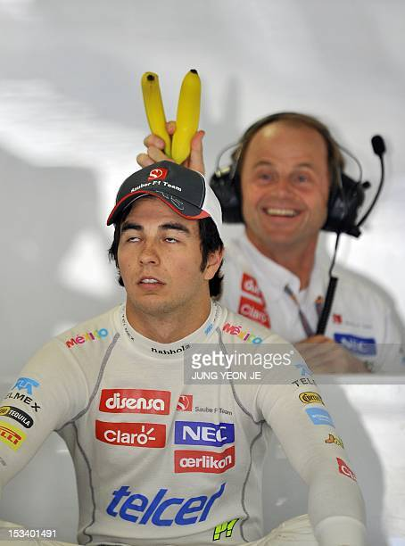 Sauber-Ferrari driver Sergio Perez of Mexico has bananas held behind his head by a team member in a pit during the first practice session of the...
