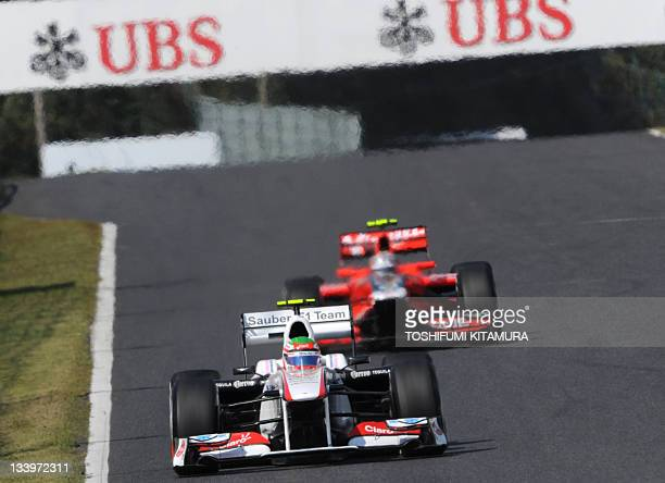 Sauber-Ferrari driver Sergio Perez of Mexico leads Virgin-Cosworth driver Jerome d'Ambrosio of Belgium on the back stretch during the first practice...