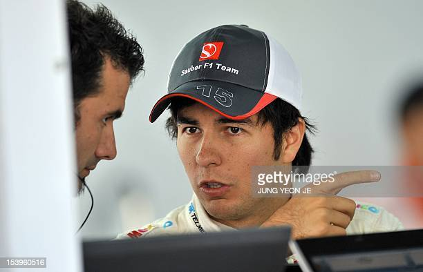 Sauber-Ferrari driver Sergio Perez of Mexico talks with a team member in the pit during the first practice session of the Formula One Korean Grand...