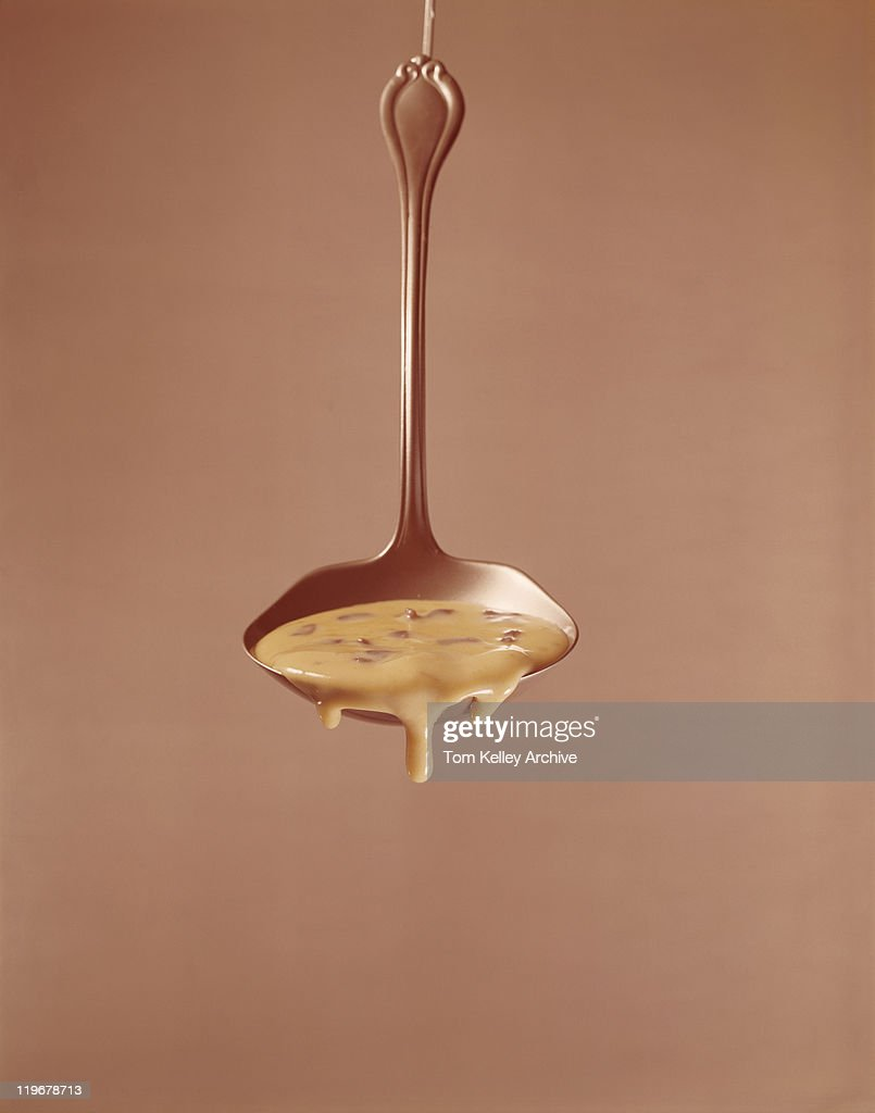 Sauce dripping from ladle against brown background : Stock Photo