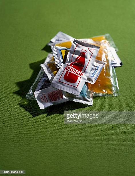 Sauce sachets on green background