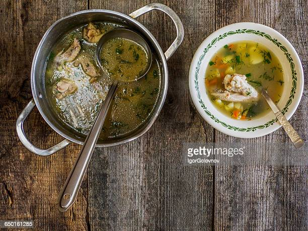saucepan and bowl of chicken soup on wooden table - chicken soup stockfoto's en -beelden
