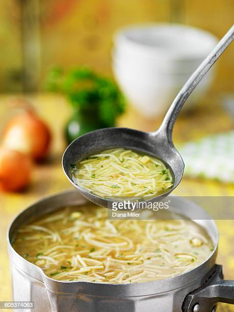 Saucepan and ladle of chicken noodle soup with onions, herbs and stock