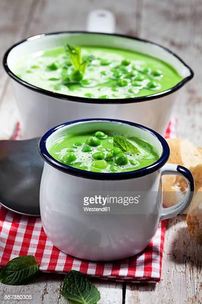 Saucepan and mug of pea soup on cloth