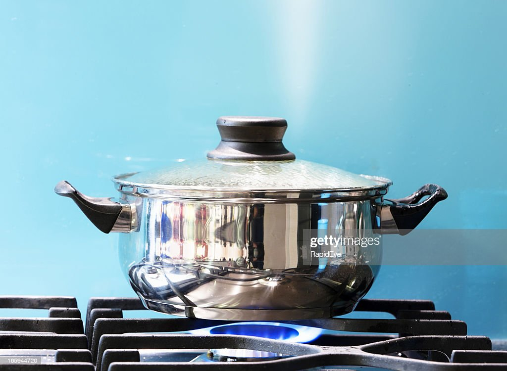 Saucepan boiling on gas stove with steam jet rising : Stock Photo