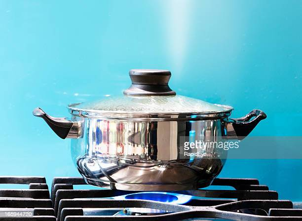 saucepan boiling on gas stove with steam jet rising - cooking pan stock pictures, royalty-free photos & images