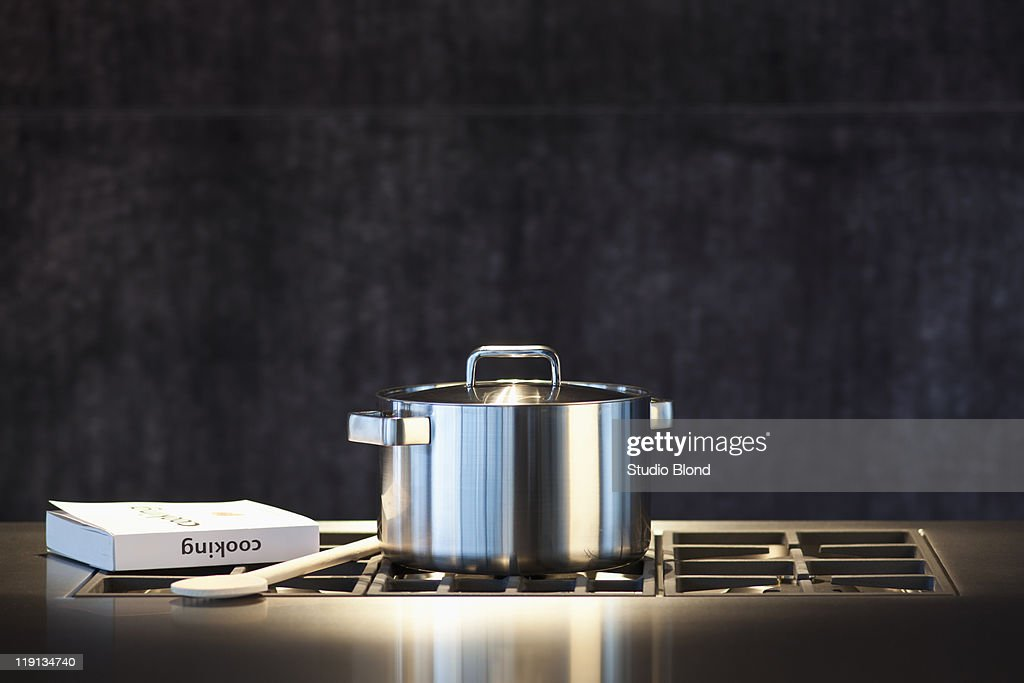 Saucepan, cookery book and wooden spoon on hob. : Stock Photo