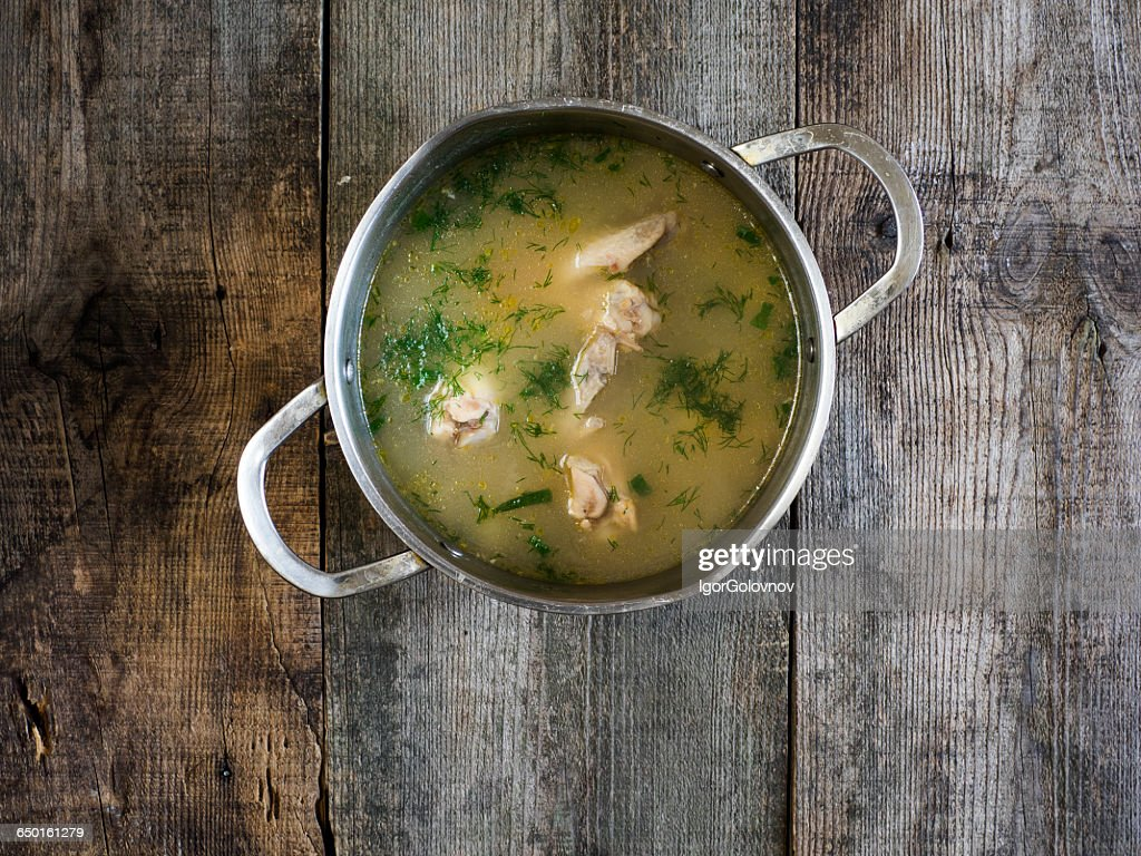 Saucepan of chicken soup on wooden table : Stock Photo