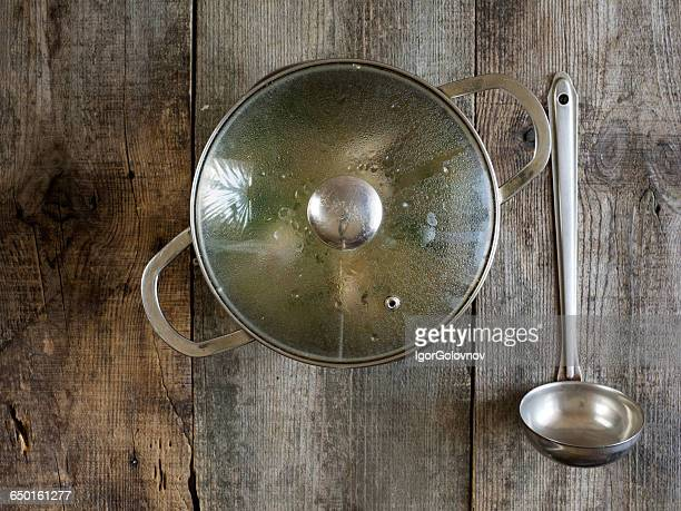 Saucepan of chicken soup with ladle on wooden table