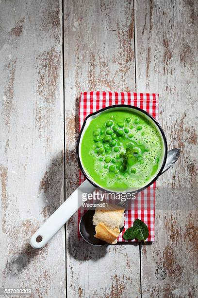 Saucepan of pea soup and sliced baguette on cloth and wood