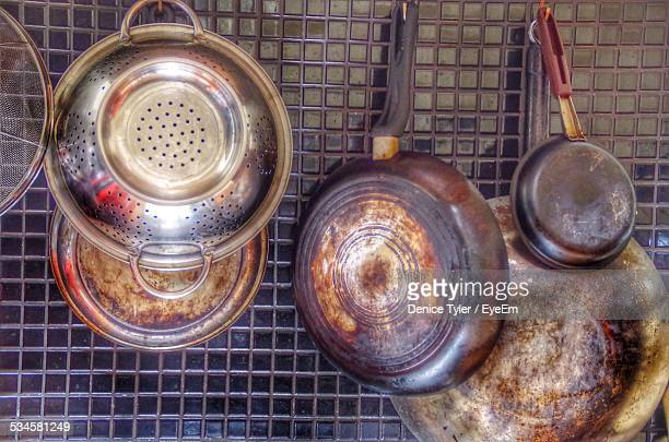 saucepans and kitchen utensils hanging on backsplash at home - saucepan stock pictures, royalty-free photos & images