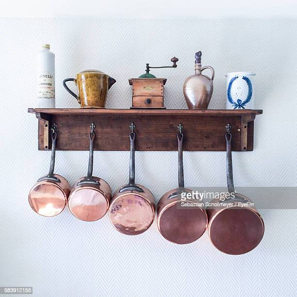 Saucepans And Utensils Hanging From Hooks Below Shelf On Wall In Kitchen At Home
