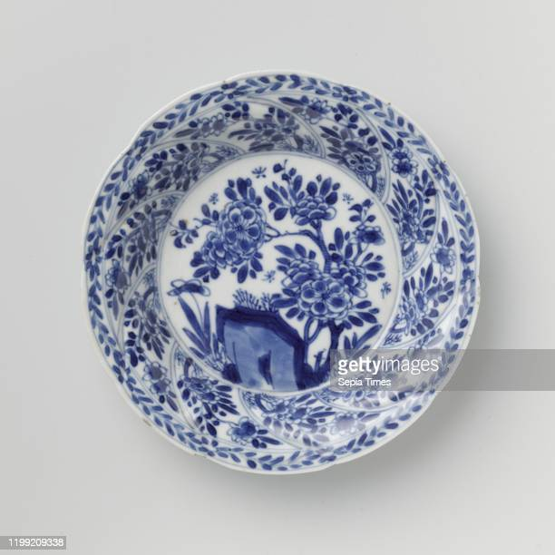Saucer with twisted panels and flower sprays, Porcelain dish with round wall modeled in ten twisted boxes, painted in underglaze blue. On the flat a...