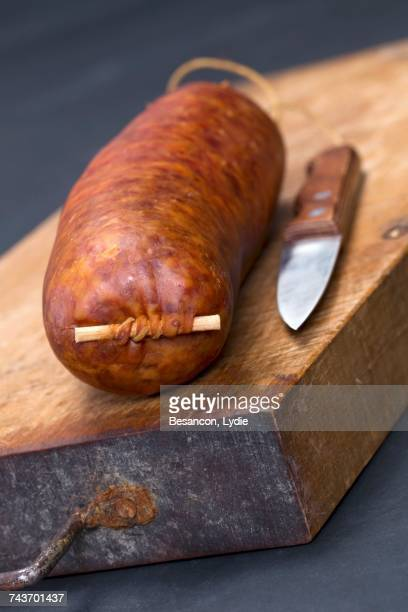saucisse de morteau (french sausage) on a chopping board with a knife - charcuterie board stock pictures, royalty-free photos & images