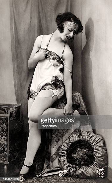 A saucy vintage postcard featuring a young lady in a suggestive pose in a state of deshabille circa 1920