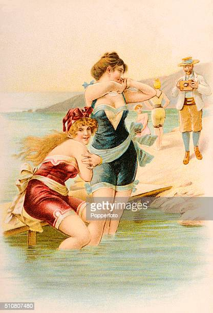 A saucy vintage postcard illustration featuring two bathing beauties on a rocky outcrop photographed by a young man with a box camera circa 1906