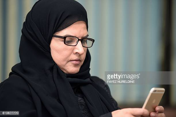 Saudi activist and campaigner Aziza alYousef checks her mobile phone during an interview in the capital Riyadh on September 27 2016 Thousands of...