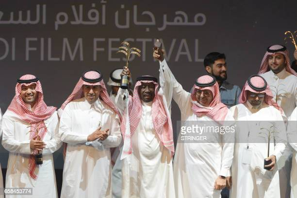 Saudi actor Saed Khader waves his honour award for his achievements at the opening ceremony of the fourth Saudi Film Festival held in Dammam City,...