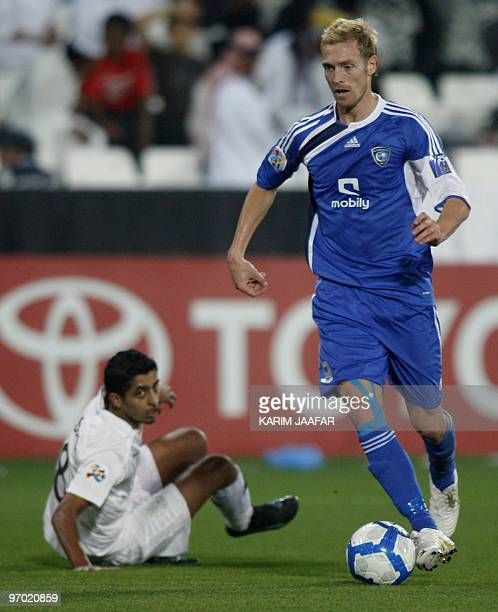 Saudi AlHilal club player Christian Wilhelmsson of Sweden vies with Qatar's AlSadd player Mesaad AlHamad at the AlSadd stadium in Doha during their...