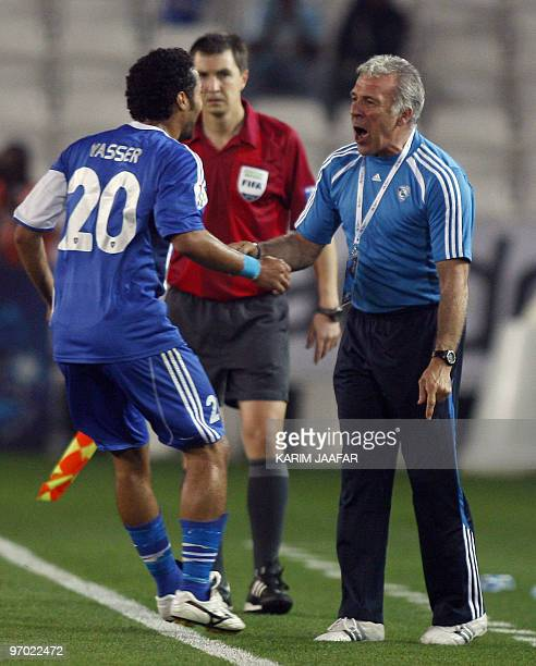 Saudi AlHilal club player Yasser alQahtani celebrates with his coach Eric Gerets of Belgium after scoring a goal against Qatar's AlSadd club during...