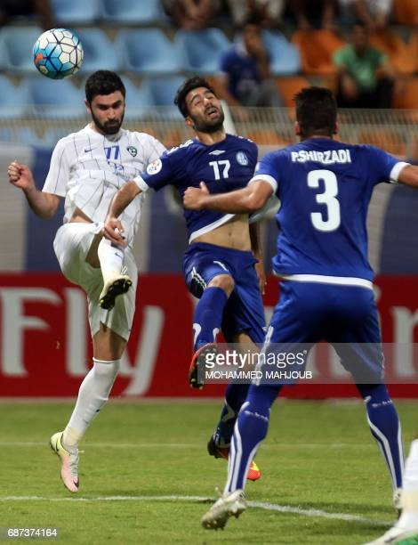 Saudi AlHilal FC's Omar Khrbin vies for the ball against Iranian Esteghlal Khouzestan FC's Salman Bahrani and Peyman Shirzadi during the AFC...