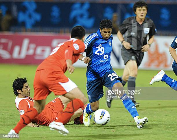 Saudi Al-Hilal Salem Mohammed dribbles past Iran's Piroozi Athletic Mohammed Mosrati and his teammate Javad Kazemeyan during their Group D, AFC...