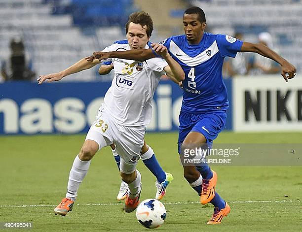 Saudi Al-Hilal's Abdullah Zori vies for the ball with Uzbekistan's Bunyodkor player Oleg Zoteev during their AFC Champions League round 16 qualifying...