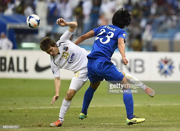 Saudi AlHilal's Tae Hwi Kwak vies with Uzbekistan's Bunyodkor player Oleg Zoteev during their AFC Champions League round 16 qualifying football match...