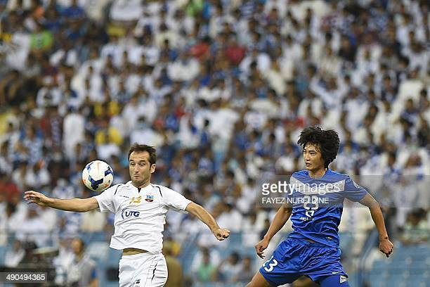 Saudi AlHilal's Tae Hwi Kwak vies with Uzbekistan's Bunyodkor player Vokhid Shodiev during their AFC Champions League round 16 qualifying football...