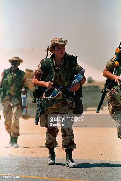 Saudi Arabia: A female Marine carries her combat gear along with two bottles of water after arriving at a Saudi airbase Wednesday.
